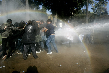 Demonstrators are hit by a police water cannon during a rally in Valparaiso