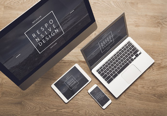 Two Computers, a Tablet, and a Smartphone on a Wooden Background Mockup