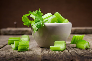 Fresh sliced celery in a white bowl on a vintage wooden background, selective focus