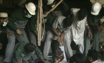 Rescue workers pull out a dead man found in the wreckage of the Pearl Continental Hotel in Peshawar