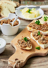 Fresh homemade Chicken liver pate with bread on a wooden board over rustic background