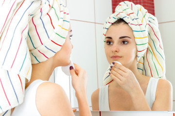 cute young girl with towel on the hair looks in the mirror and rubs your face with a cotton disk