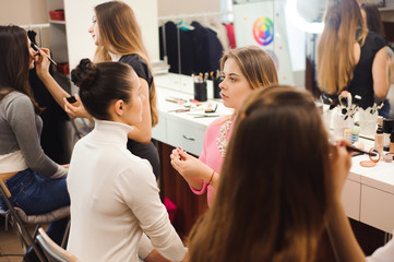 Three professional make-up artists work with beautiful young women. School of professional make-up