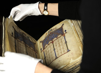 Conservator June Wallis turns a page of an 11th century Byzantine manuscript during a photocall at the Royal Academy of Arts in London