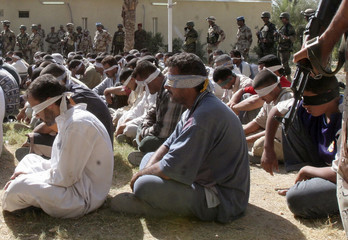Detained suspected insurgents sit on the grounds at an army headquarters in Baquba