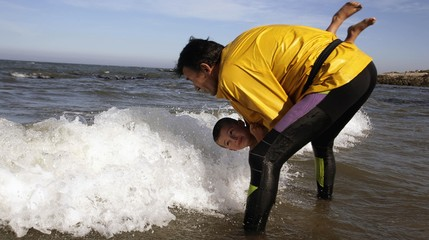 A man holds a child as he is dipped into the sea as part of a bath marking St. Bartolomeu day in the village of San Bartolomeu