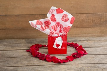 Gift box surrounded with red rose petals place in heart shape