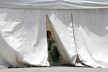 A patient diagnosed with the Influenza A (H1N1) flu sits inside an isolation tent outside a government hospital in Quezon City