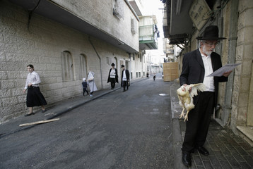 An Ultra-Orthodox Jewish man holds a chicken as he prays during Kaparot in Jerusalem