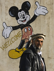 An Afghan man walks past a Mickey Mouse wall painting in Kabul