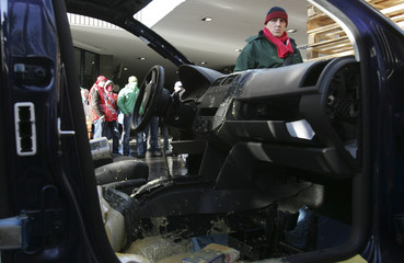 Volkswagen workers look at a car blocking the main entrance of Volkswagen's Brussels plant
