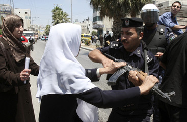 Palestinian woman scuffles with member of Palestinian security forces during protest in Hebron