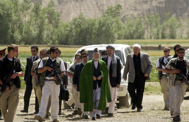 Afghan President Karzai is surrounded by security officials as he arrives for a visit to Bamiyan.