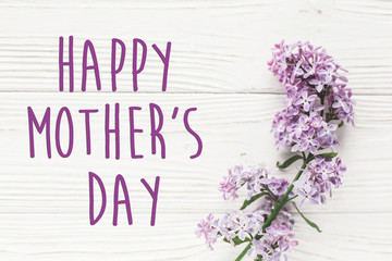 happy mother's day text sign. greeting card. gentle purple lilac flowers on white rustic wooden background. tender soft image. mothers day concept. flat lay