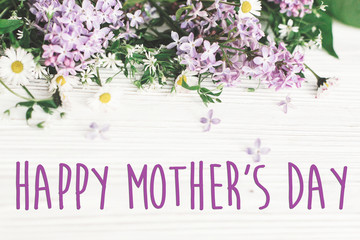 happy mother's day text sign. greeting card. gentle pink lilac flowers and daisy on white rustic wooden background. tender soft image. mothers day concept.