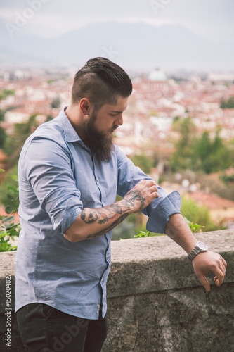 3501f0a7219 Man adjusts his shirt sleeves. Tattooed guy straightens the sleeve ...