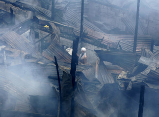 A resident salvages his belongings amidst burnt houses after a fire charred hundreds of houses in a neighbourhood in Quezon City Metro Manila