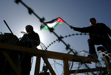 A Palestinian demonstrator confronts Israeli troops during a protest in Bilin