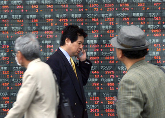 Japanese passers-by look at share prices on a stock quotation board outside a securities brokerage i..