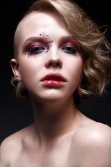 A young girl with a short haircut and bright creative makeup. A beautiful model with sparkles on the face and red lips. Evening makeup, beauty of the face. Photo is taken in a studio.