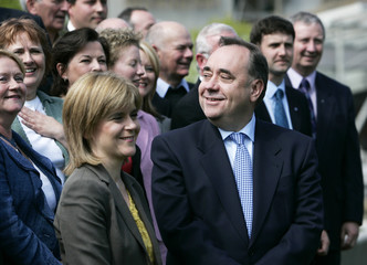 Scottish National Party leader Salmond stands with his deputy leader Sturgeon outside the Scottish Parliament building in Edinburgh