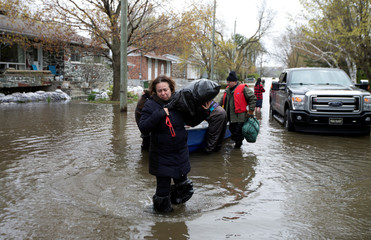 Mina Tayarani carries a bag of her belongings as she is evacuated from her home in a flooded residential neighbourhood in Ile Bizard, Quebec, Canad
