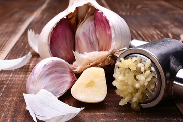 Sliced garlic, garlic clove, garlic bulb and garlic press on wooden table.