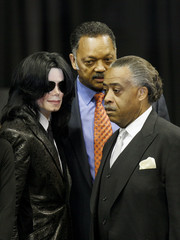 Michael Jackson stands with Al Sharpton and Jesse Jackson near the end of a public viewing and funeral for legendary singer James Brown in Augusta