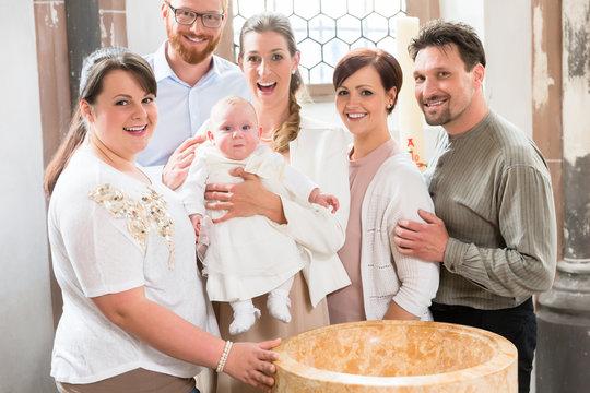 Eltern und Taufzeugen versammeln sich mit Baby nach der Taufe in der Kirche