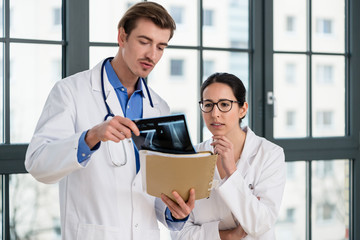 Experienced physician and his colleague interpreting the radiograph of the knee of a patient
