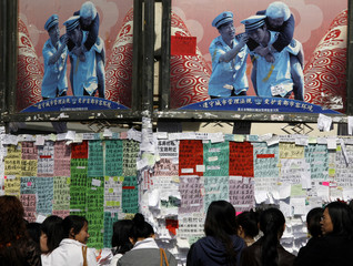Promotional poster for Beijing Olympic Games hangs above crowd of people gathered around notice board advertising rental properties in central Beijing