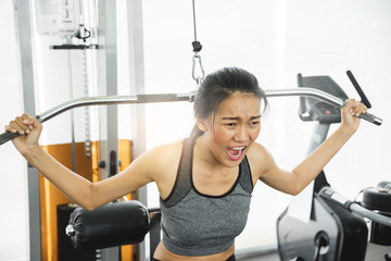 Asian woman in sportswear exercising with exercise machine at the gym.