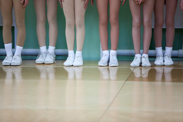 Children legs of aerobic athletes wearing in white sport boots standing in line in gym