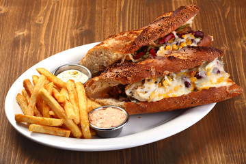 steak sandwich with cheese and potatoes and sauce
