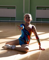 Portrait of an eight years old girl gymnast on the gym floor in the starting position before the performance