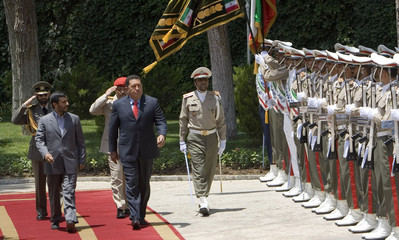 Iranian President Mahmoud Ahmadinejad and Venezualan President Hugo Chavez  review the honour guard during a welcoming ceremony in Tehran