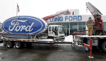 Workers remove the Ford logo signs from Al Long Ford auto dealership in Warren, Michigan