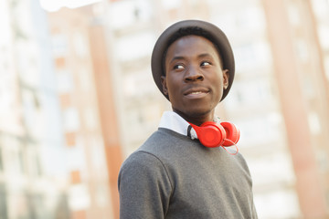 African american man with hat and headphones in city