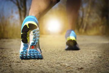 Back view of male muscular feet in sneakers walking on sidewalk in spring sunny day