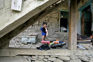 Kashmiri girl stands amid the rubble of her destroyed house in Pingal