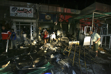 Men search for the dead or wounded after a bomb destroyed a bakery and a butcher shop in a market in New Baghdad