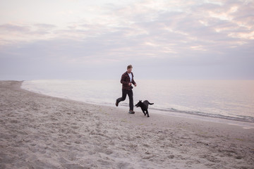 young man run and playing with black dog on the beach