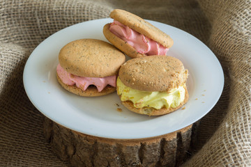 Cookies sandwich on a white plate. Delicious dessert. Composition in a rustic style.