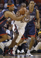Milwaukee Bucks' Redd tries to steal the ball from Charlotte Bobcats' Dudley as Hollins comes into the play during their NBA game in Charlotte