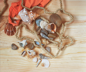 Sea shell, rope and stones on wooden surface.