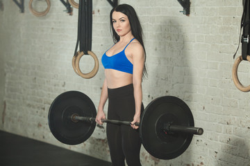 Beautiful young girl with a barbell in a squat in a perfect figure
