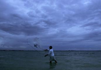 Sanibel Island resident Bryan Picco throws cast net as skies from Hurricane Wilma loom