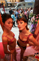Models present underwear creations at a display window in Hong Kong