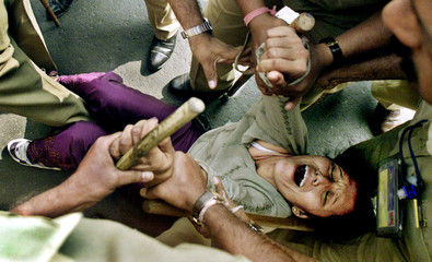 INDIAN POLICEMEN DRAG A TIBETAN WOMAN DURING A DEMONSTRATION IN BOMBAY.
