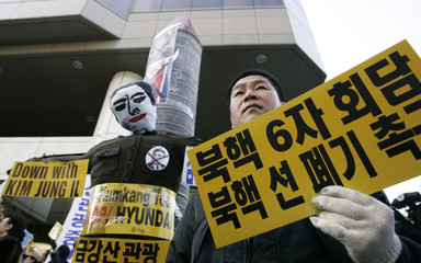 Protester holds a placard next to a mock missile model and an effigy of North Korean leader Kim Jong-il in Seoul during a rally demanding the dismantle of North Korea's nuclear programme